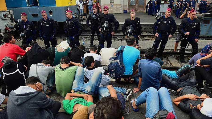 Policías antidisturbios en la estación de Keleti, en Budapest, frente a refugiados que esperan para tomar un tren a Alemania