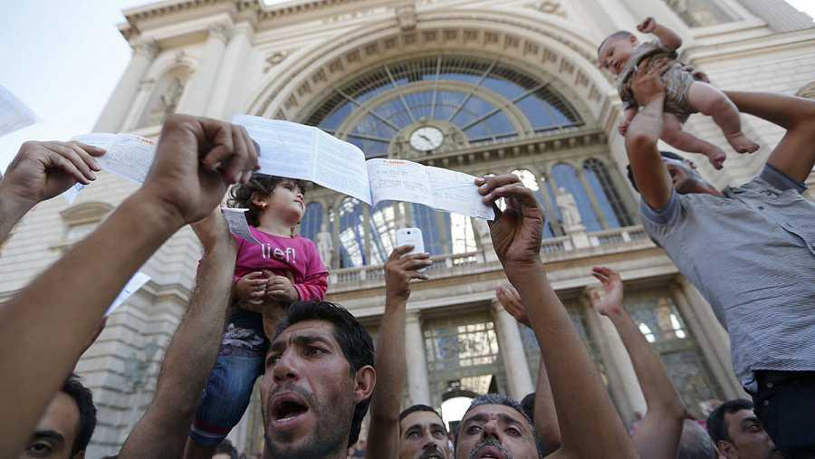 Refugiados muestran sus billetes tras ser desalojados de la estación de trenes de Keleti, en Budapest, cuando pretendían llegar a Alemania