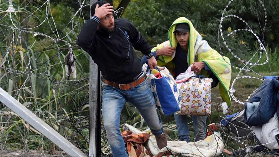 Refugiados cruzan a través de un agujero en la alambrada que separa Serbia de Hungría cerca de Roszke, en este último país. AFP PHOTO / ATTILA KISBENEDEK