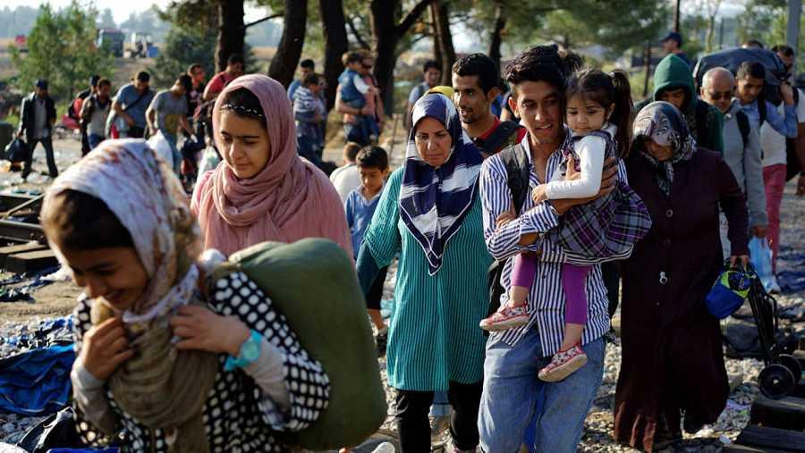 Refugiados cruzan la frontera de Macedonia con Grecia.