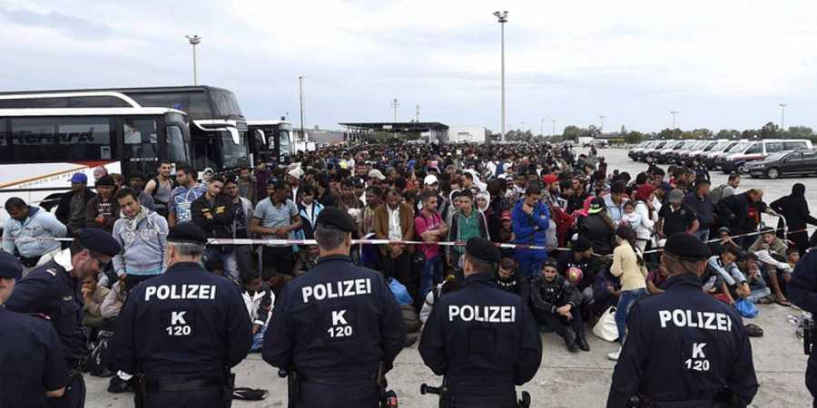 Agentes de policía vigilan a un grupo de refugiados en la frontera entre Hungría y Austria, en Nickelsdorf (Austria)