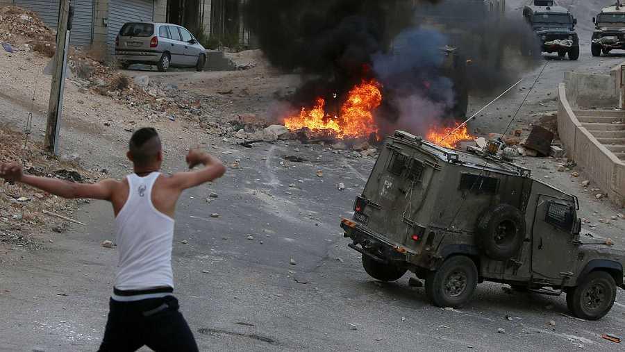 Un joven palestino arroja piedras contra los vehículos de los soldados israelíes en Nablus, Cisjordania, el 6 de octubre de 2015 AFP PHOTO / JAAFAR ASHTIYEH