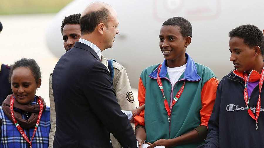 El ministro de Interior italitano, Angelino Alfano, saluda a los refugiados eritreos antes de que partan desde Roma a Estocolmo. REUTERS/Remo Casilli