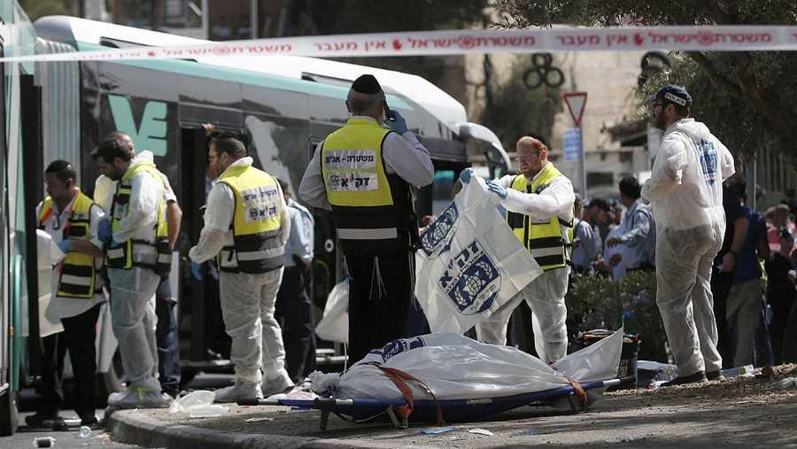 Voluntarios israelíes junto a un cuerpo en el lugar en el que dos palestinos han abordado un autobús y han atacado a sus ocupantes, cerca de la localidad palestina de Yabal Mukaber, en Cisjordania. AFP PHOTO / THOMAS COEX