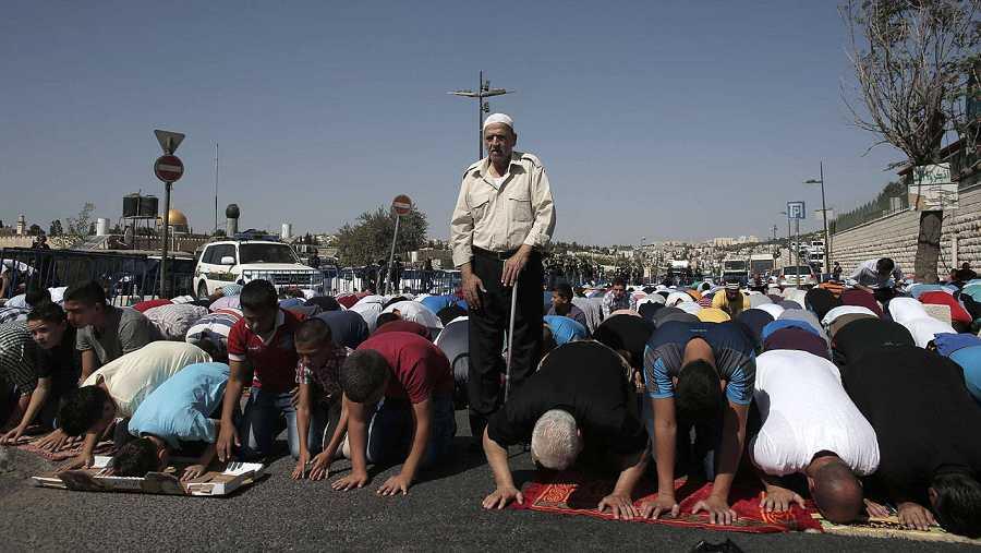 Fuerzas de seguridad de Israel montan guardia mientras musulmanes palestinos rezan en el barrio de Ras Al Amud, en Jerusalén, el 16 de octubre de 2015. Israel ha restringido la entrada en la Explanada de las Mezquitas a los varones de más de 40 años.