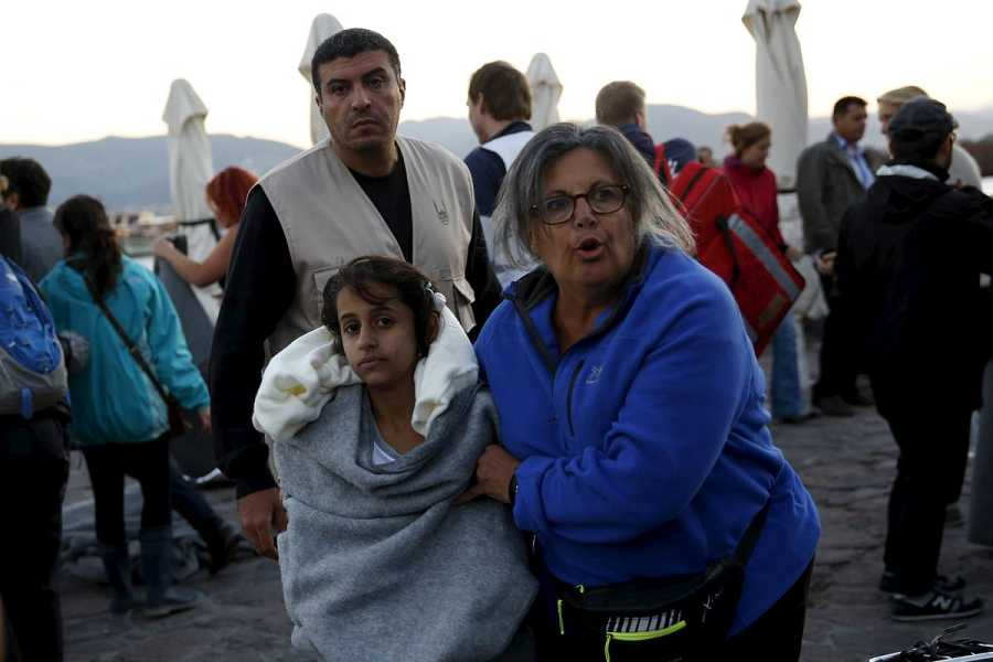 Una voluntaria acompaña a una chica al llegar a Lesbos