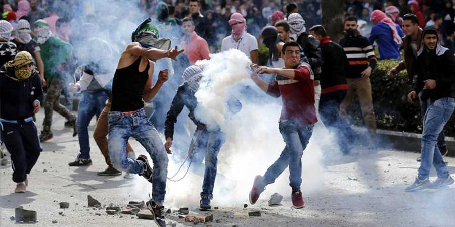 Manifestantes palestinos lanzan piedras contra soldados israelíes durante enfrentamientos en la ciudad cisjordana de Hebrón