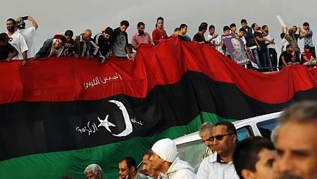 Ciudadanos libios sujetan una bandera nacional en una manifestación contra el acuerdo de la ONU