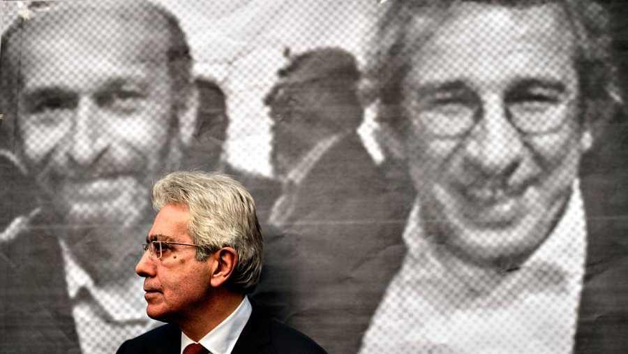 Un hombre se apoya sobre una imagen de Erdem Gül y Can Dündar en la sede del diario 'Huriyet'