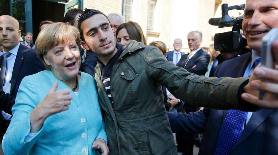 Merkel se hace un 'selfie'con un refugiado a la salida de un centro de acogida.