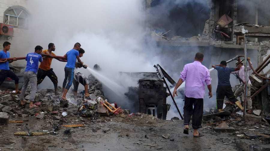 La gente intenta extinguir uno de los fuegos causados por el atentado de Adén