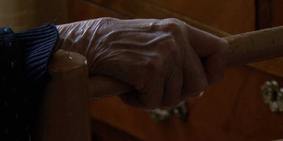 Detalle de la mano de Carmen agarrando la silla