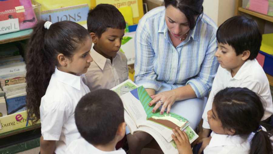 Profesora leyendo con sus alumnos