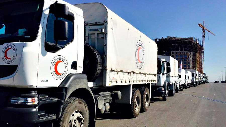 Varios camiones de la Media Luna Roja con ayuda humanitaria esperan en Damasco, antes de partir hacia zonas sitiadas por el régimen