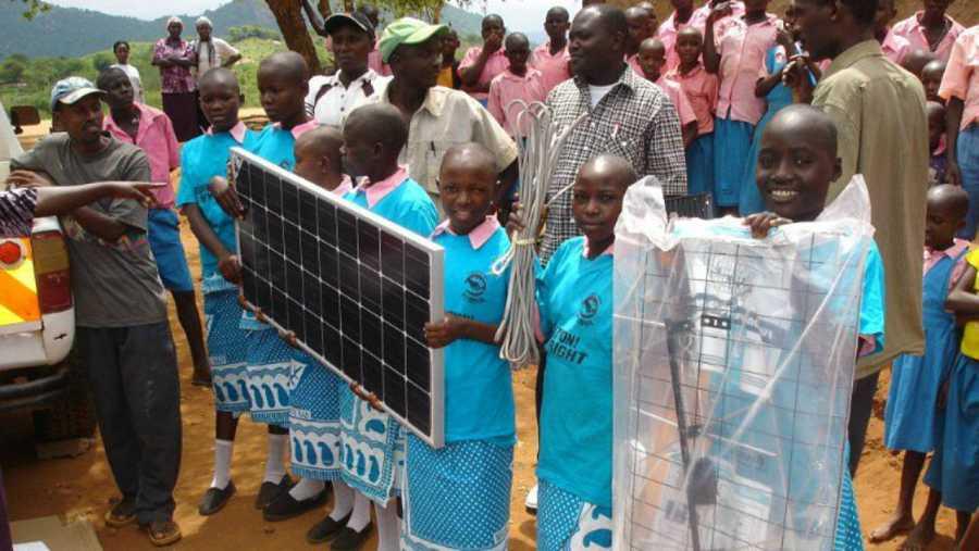 Unas niñas sostienen unos paneles solares en Kamaindi