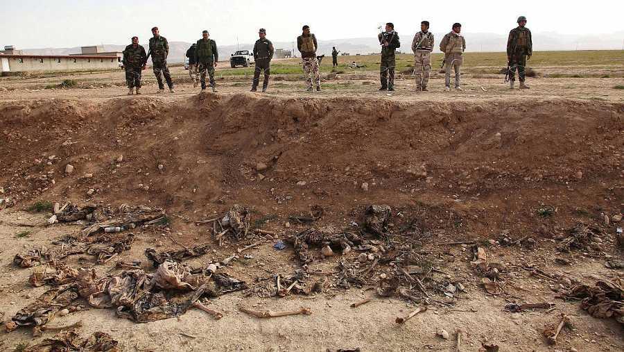 Milicianos kurdos (peshmerga) ante una fosa común en los alrededores de Sinjar, en Irak. REUTERS/Ari Jalal