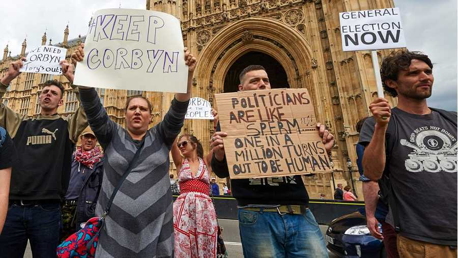 Manifestantes con pancartas protestan frente al Parlamento británico en Londres