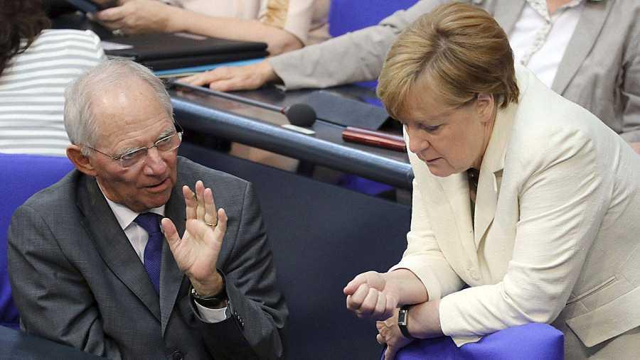 La canciller alemana, Angela Merkel, conversa con el ministro de Finanzas, Wolfgang Schäuble, después de exponer ante el Bundestag las consecuencias del 'Brexit'.