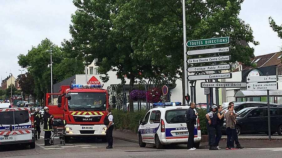 Ambulancias y coches de policía apostados junto a la iglesia de Saint Etienne du Rouvray, donde dos hombres han secuestrado a varias personas.