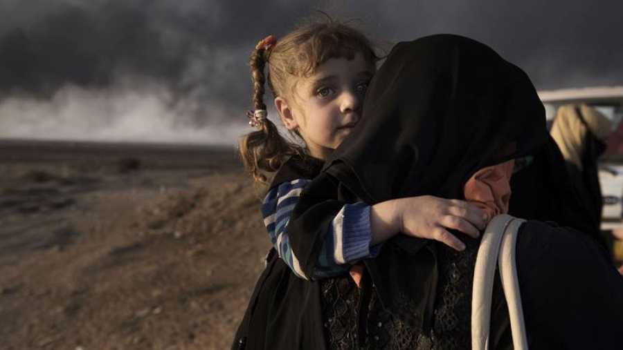Una mujer desplazada lleva a su hija en el 'check point' de Qayyara, al sur de Mosul el 31 de octubre de 2016.