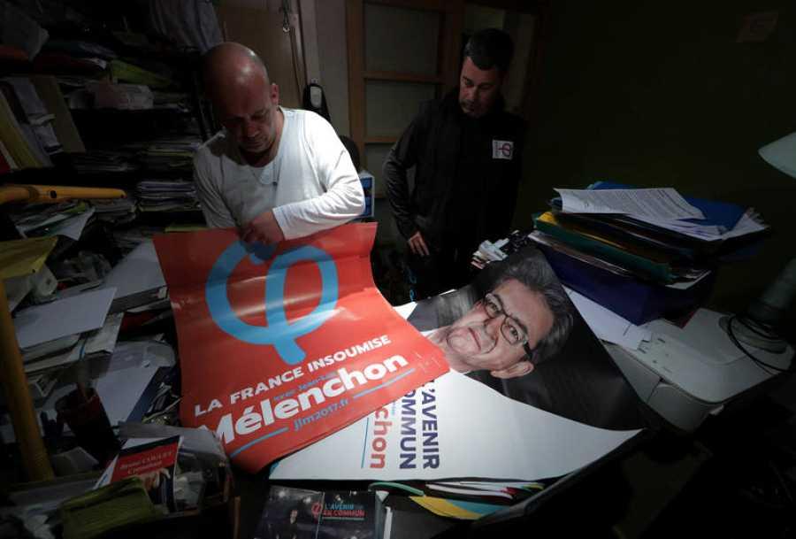 Un militante del Partido de Izquierda prepara varios carteles con la imagen del candidato, Jean-Luc Mélenchon