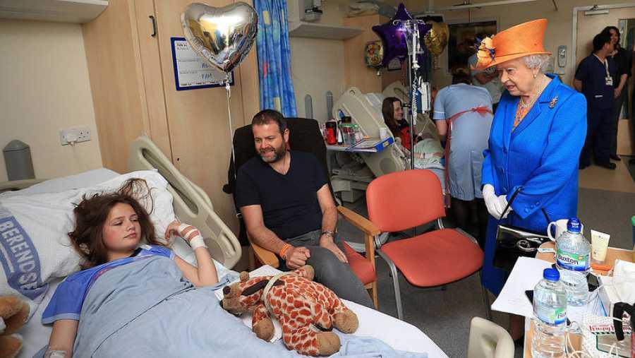 La reina Isabel II de Inglaterra habla con Evie Mills, de 14 años, y sus padres, durante su visita a los heridos del atentado de Mánchester en el Royal Manchester Children's Hospital