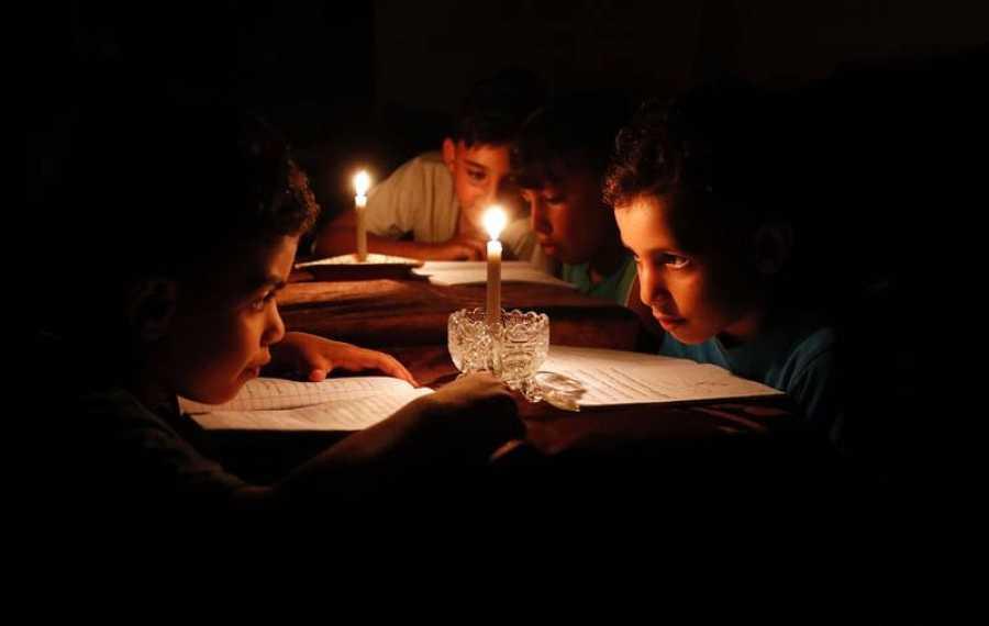 Niños palestinos leen a la luz de las velas debido a los cortes de electricidad en Gaza.