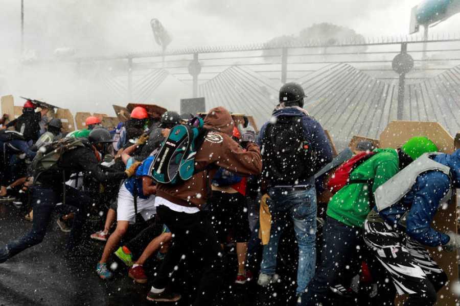 Los manifestantes echan abajo las vallas de la base militar de La Carlota, en Caracas.