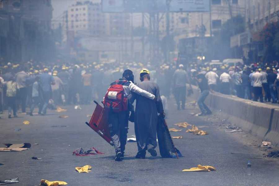 Un miembro de la Cruz Roja ayuda a uno de los manifestantes heridos en las protestas ante el puesto de control de Qalandiya, en Cisjordania