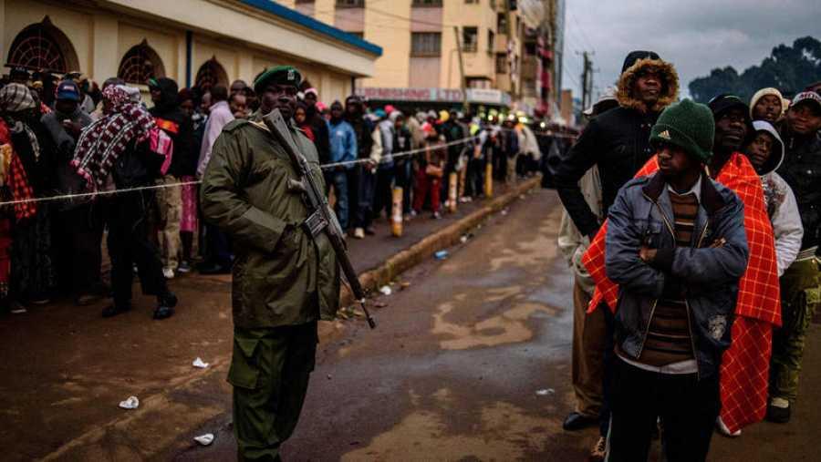 Efectivos de seguridad kenianos vigilan las colas de votantes en un colegio electoral de Eldoret, Kenia