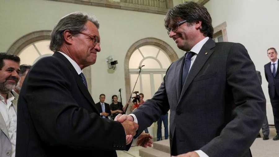 Puigdemont saluda a Mas al termino de su declaración institucional.
