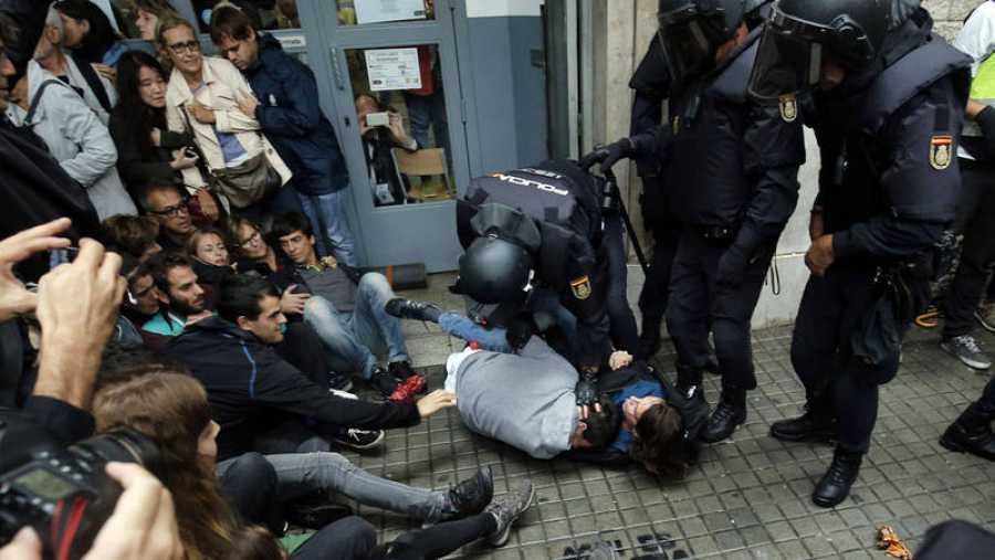Agentes de Policía Nacional inmovilizan a dos personas en el exterior de un colegio electoral en Barcelona