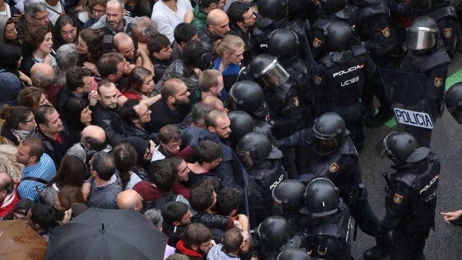 Los antidisturbios de la Policía Nacional bloquean la entrada de personas concentradas en el exterior de un colegio electoral en Barcelona