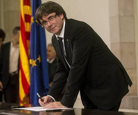Carles Puigdemont firma un documento después de comparecer ante el pleno del Parlament