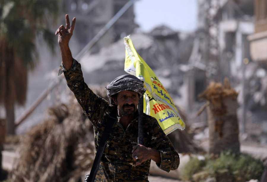 Un combatiente de las milicias de las FDS hace el signo de la victoria en Raqqa
