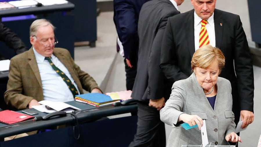 La canciller alemana Angela Merkel vota en el Parlamento. Detrás, el diputado de AfD Albrecht Glaser