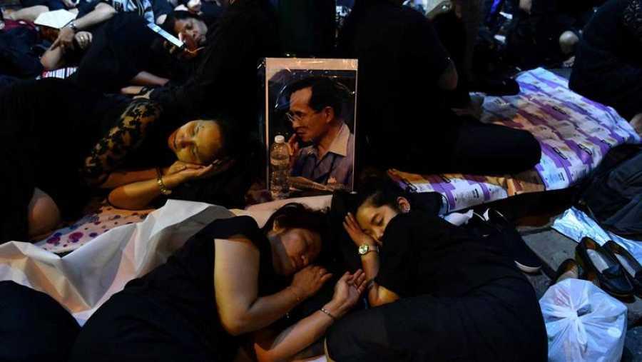 Unas mujeres duermen en la calle antes de la procesión por el funeral