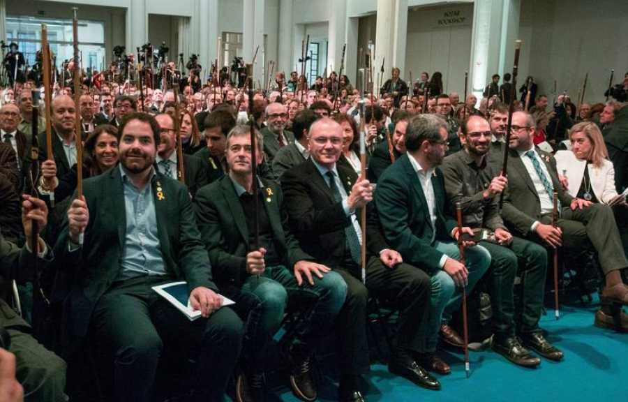 Los alcaldes independentistas congregados en Bruselas levantan su vara de mando, símbolo de su poder municipal.