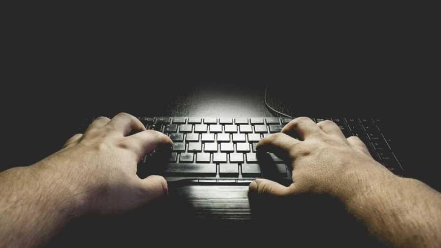 Un hombre escribe en el teclado de su ordenador