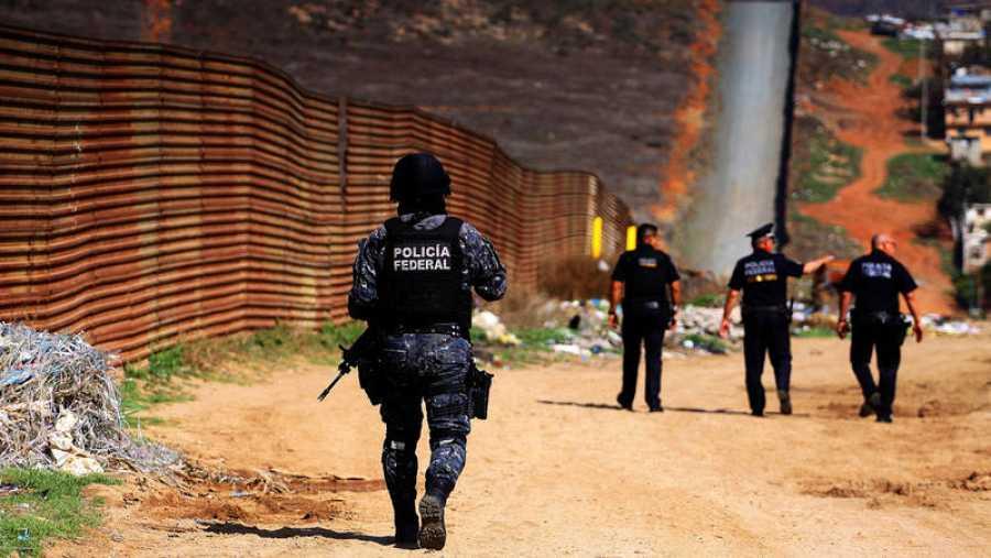 Policías federales custodian la valla fronteriza que delimita a México con EE.UU.