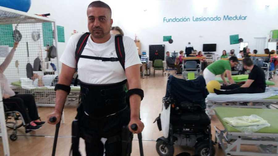 Genaro se ayuda de un exoesqueleto para caminar.