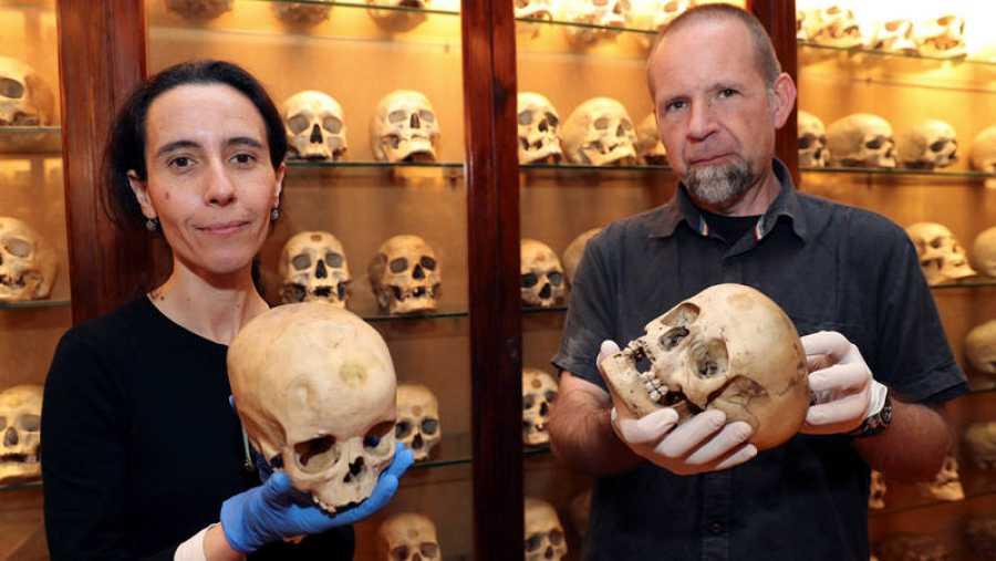 La conservadora del Museo Canario, Teresa Delgado, y el arqueólogo de la Universidad de Las Palmas de Gran Canaria, Javier Velasco, muestran dos de los cráneos de niños estudiados.