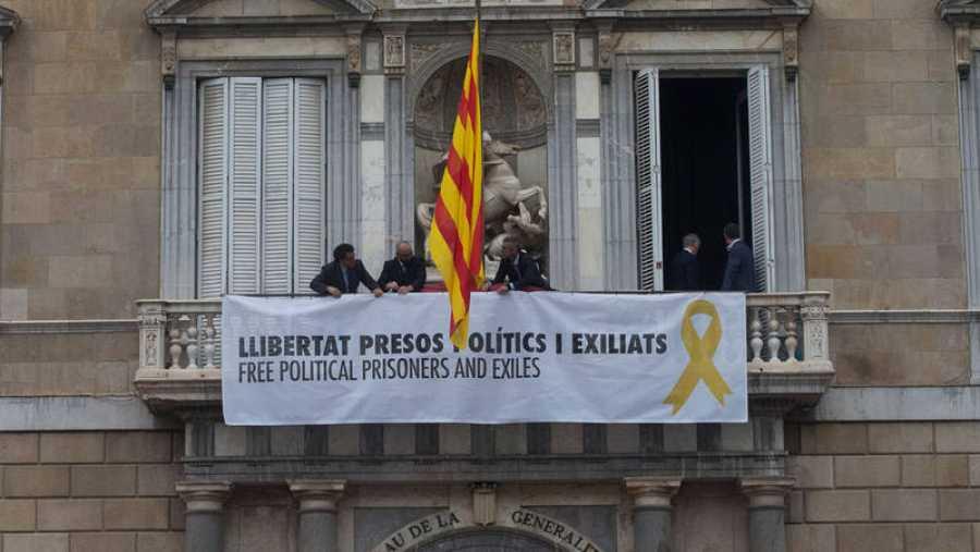 Trabajadores de la Generalitat colocan en el balcon del Palau una pancarta por los