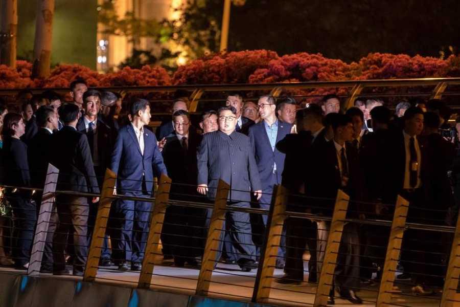 Kim Jong-un y su séquito cruzan a pie el puente Jubilee de Singapur, durnate su paseo nocturno