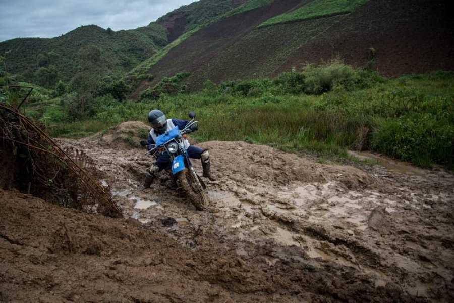Un motorista se desplaza por un camino embarrado hacia Numbi (R.D. Congo)