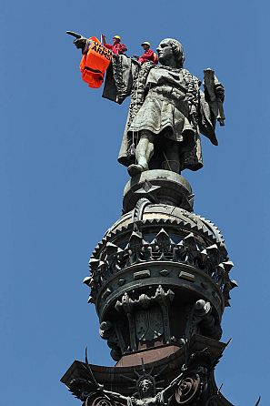 Activists from the Spanish Proactiva Open Arms charity place a life jacket on the Christopher Columbus statue in Barcelona