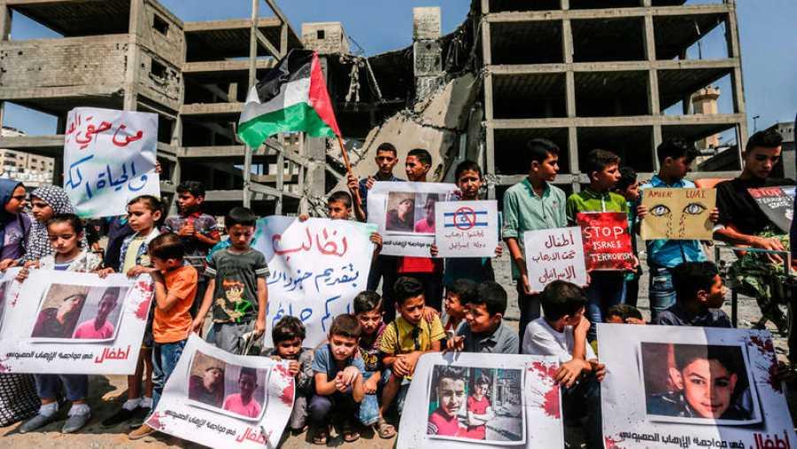 Jóvenes palestinos muestran fotografías de los dos adolescentes muertos junto al edificio atacado por Israel