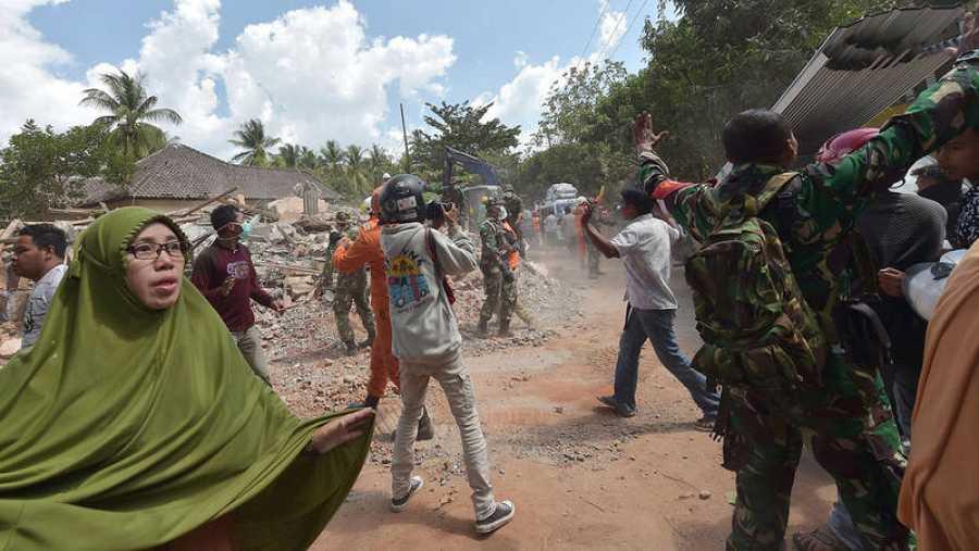 Varias personas se ven sorprendidas por el nuevo terremoto en Lombok (Indonesia) mientras participaban en las labores de desescombro del seismo anterior. Fuente: ADEK BERRY / AFP