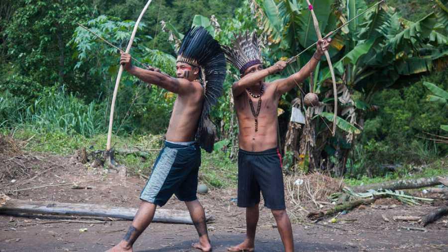 Dos jóvenes indígenas se disponen a disparar sus arcos.