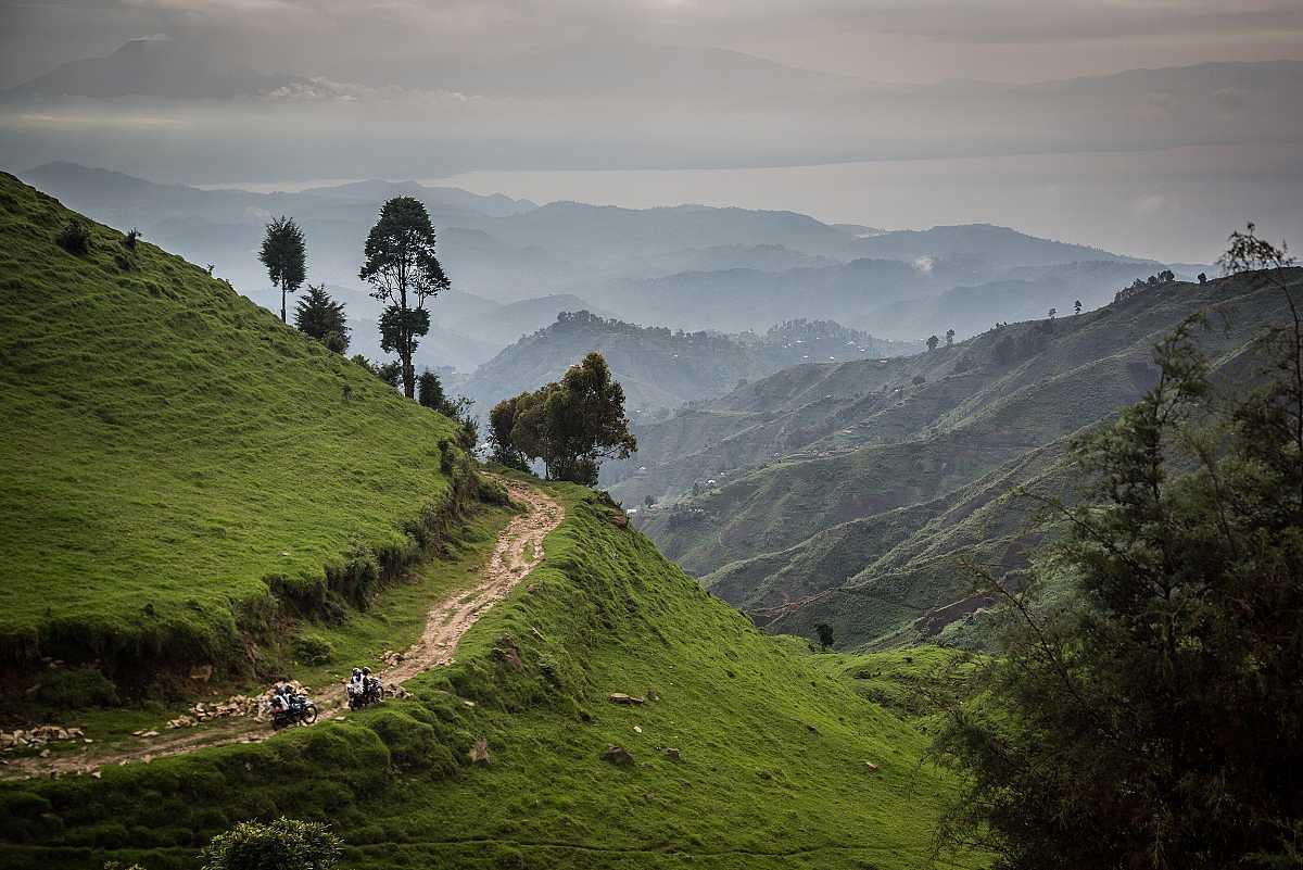 Unos motoristas avanzan por un camino en la ladera de una montaña cubierta de vegetación, camino de Numbi.